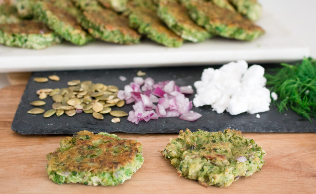 Two green pea fritters on fried and one baked on a slate plate