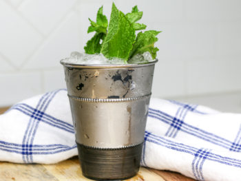 Easy mint julep on a wooden cutting board with a blue and white napkin