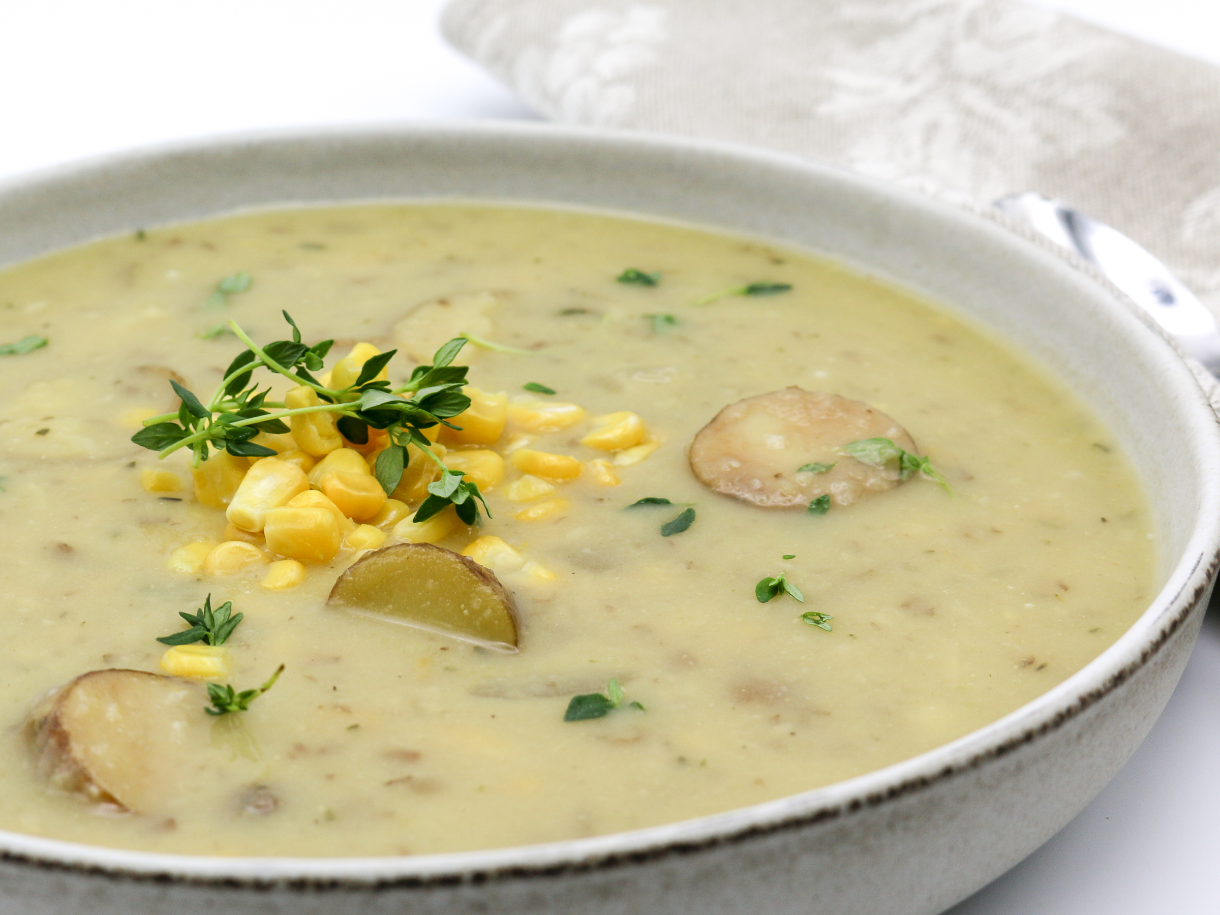 Close up of potato and corn soup with thyme herbs