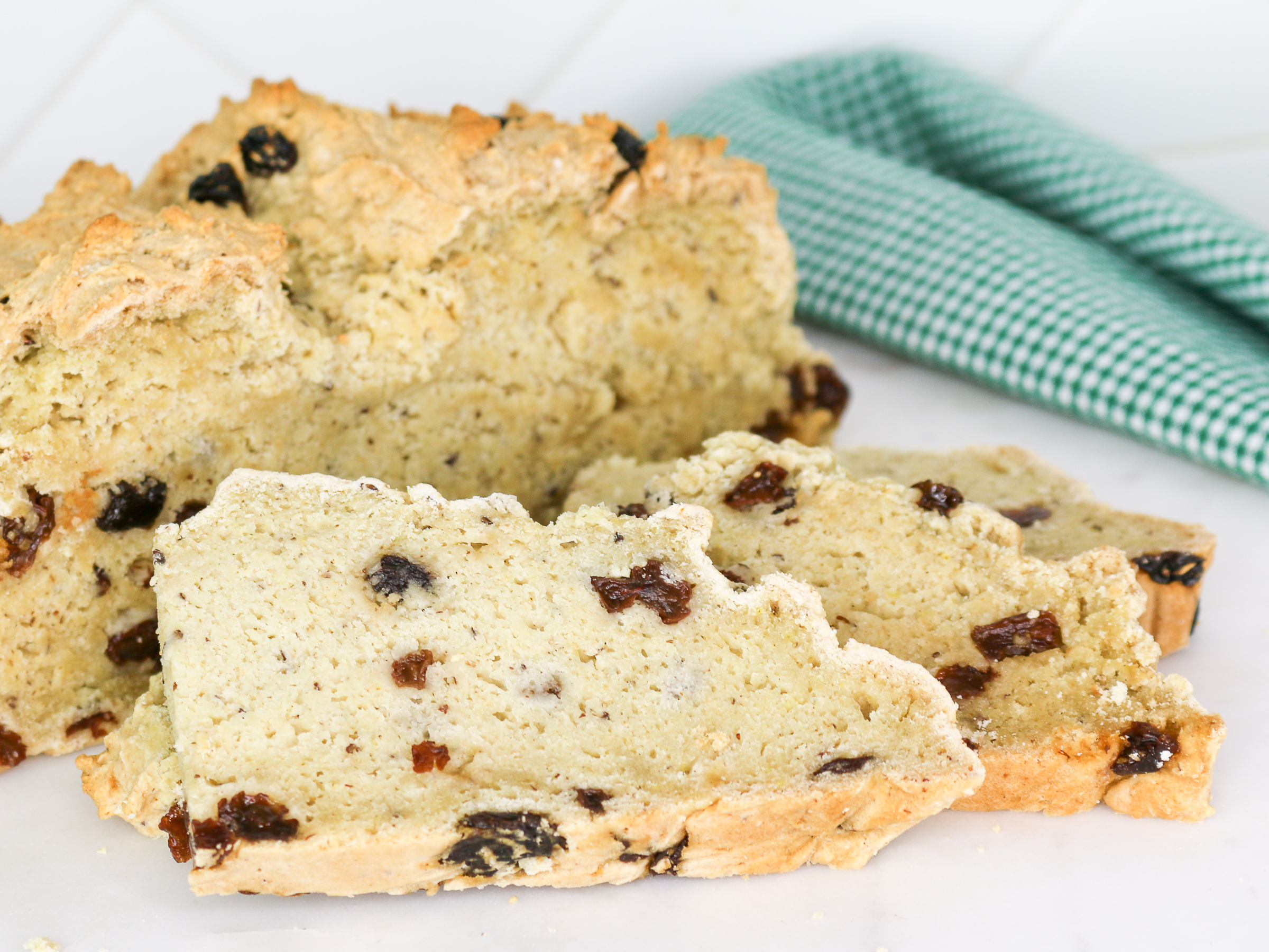 Sliced Irish soda bread on white plate with green and white naplin