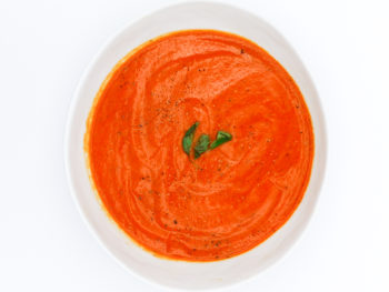 White soup bowl with roasted red pepper with fresh oregano