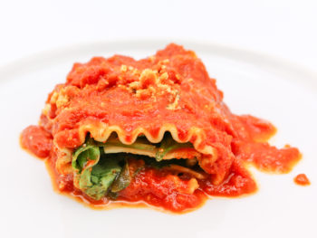 White plate with spinach lasagna roll-up