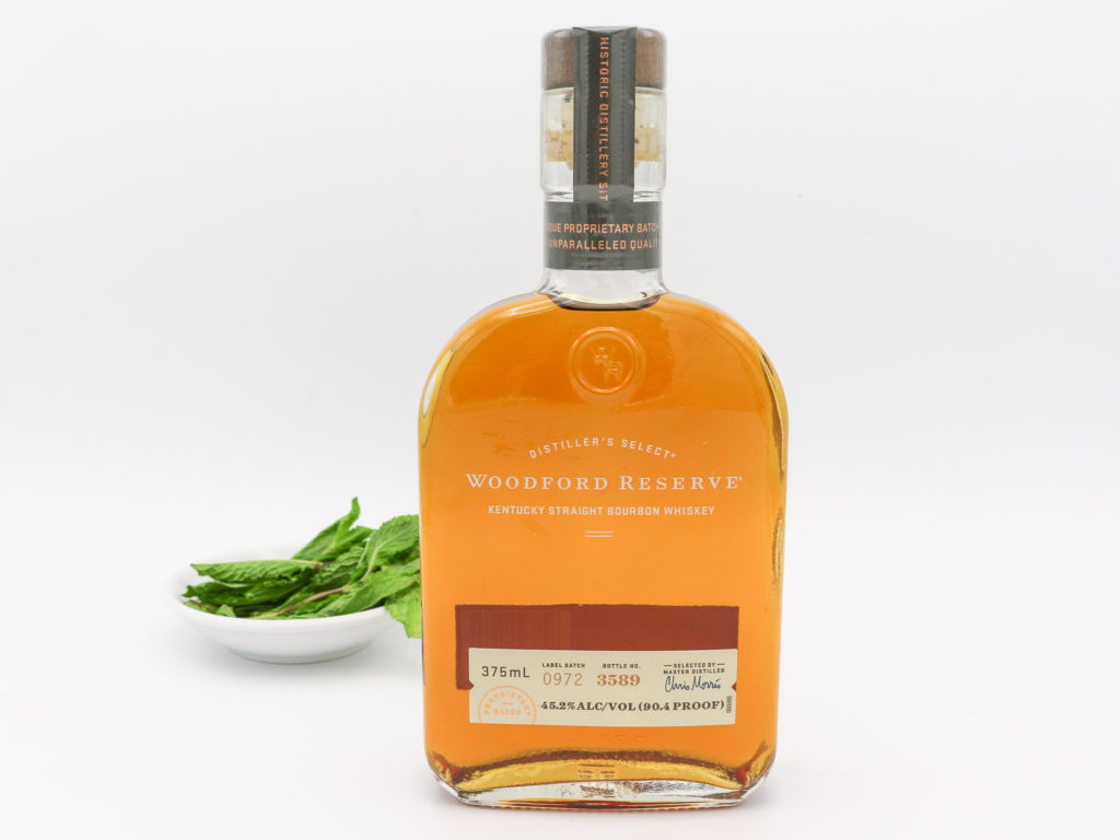A bottle of Woodford Reserve Kentucky Straight Bourbon Whiskey with mint leaves in the background