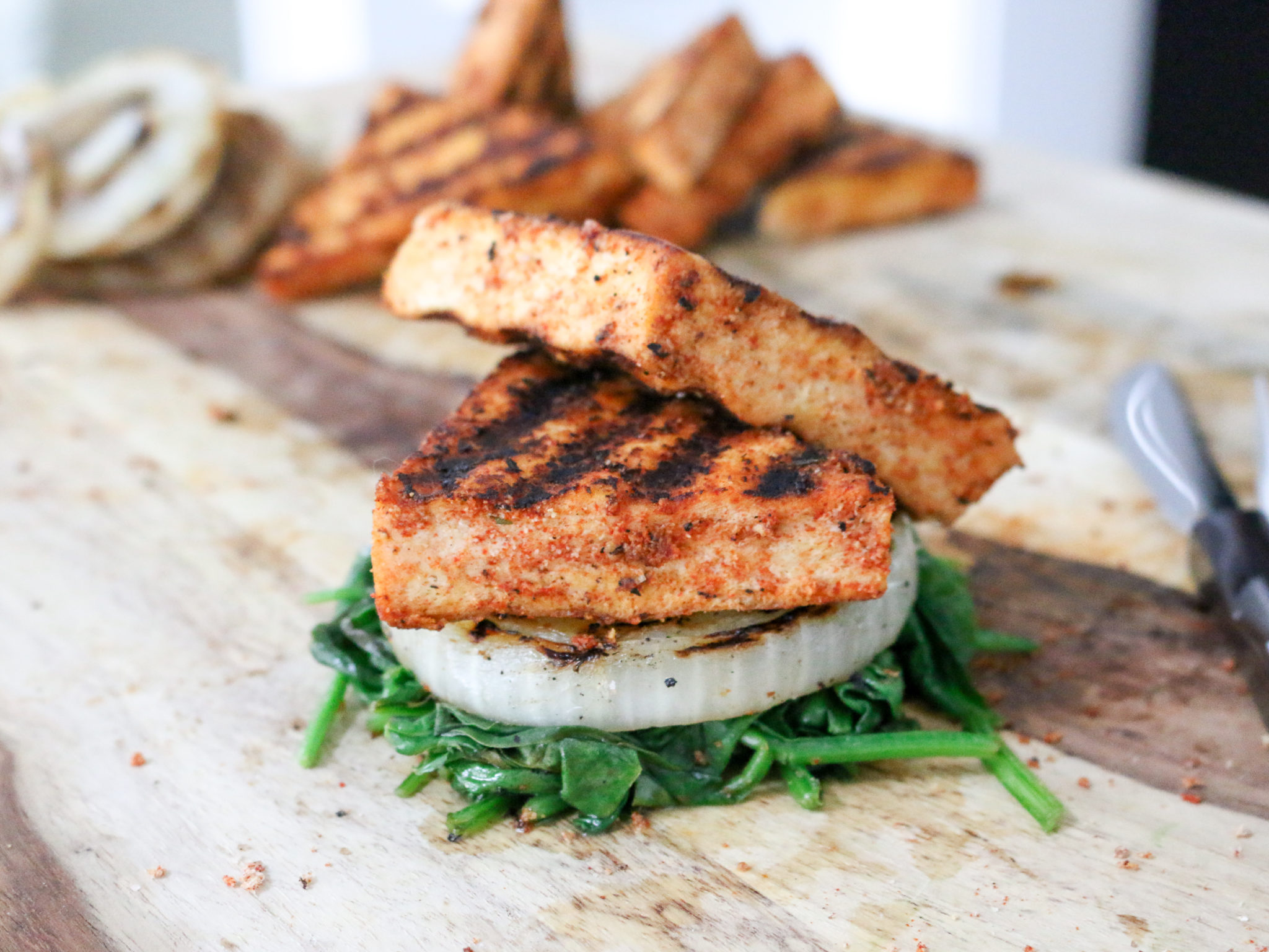 Grilled tofu steak on a wood board with onion and spinach