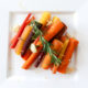 Square white plate with cooked rainbow carrots, garlic, and rosemary sprig