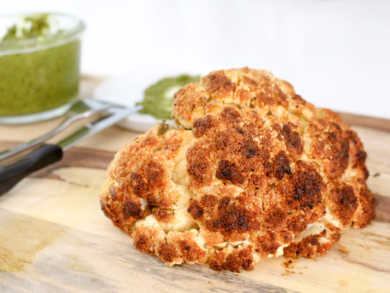 Grilled cauliflower head on a wood cutting board